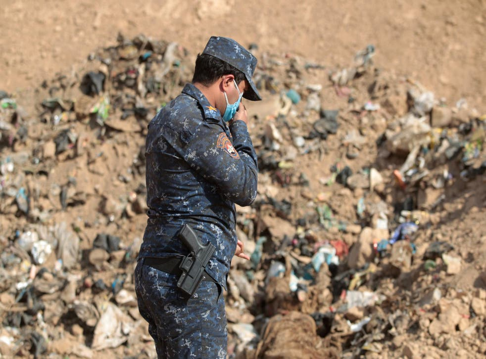 A member of the Iraqi forces checks a mass grave they discovered in Iraq in 2016, after they recaptured the area from Isis