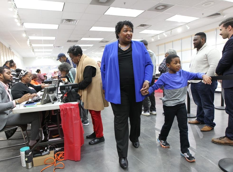 Stacey Abrams walks to a voting machine with her nephew in Decatur, Georgia