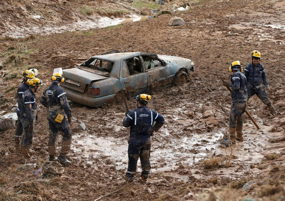 f472c2201 Civil defense members look for missing persons after rain storms unleashed  flash floods, in Madaba