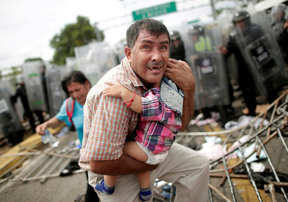 A Honduran Man Protects His Child After Migrants Part Of Caravan Trying To Reach