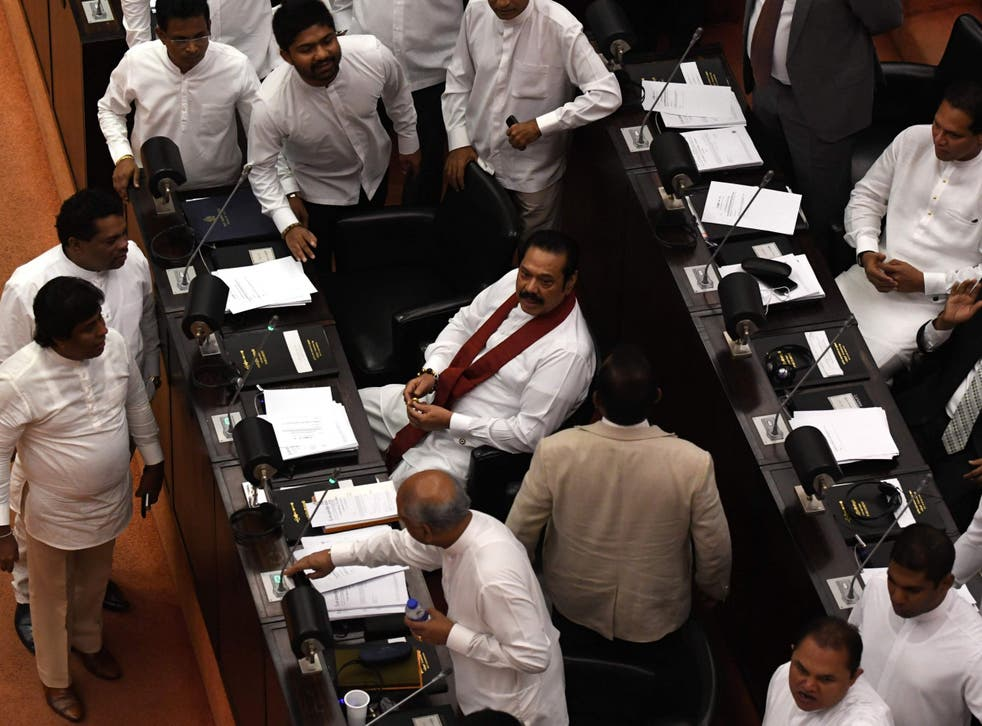 Sri Lanka's former president and currently appointed prime minister Mahinda Rajapaksa (C) attends the parliament session in Colombo