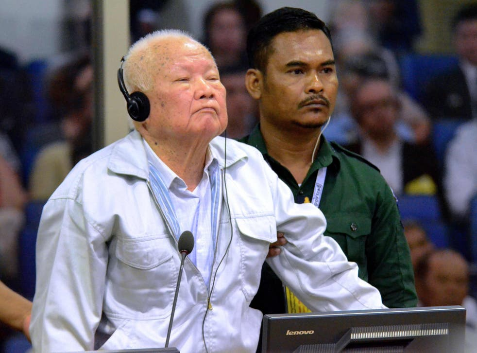 Khieu Samphan (L) stands during his verdict in court at the international tribunal in Phnom Penh