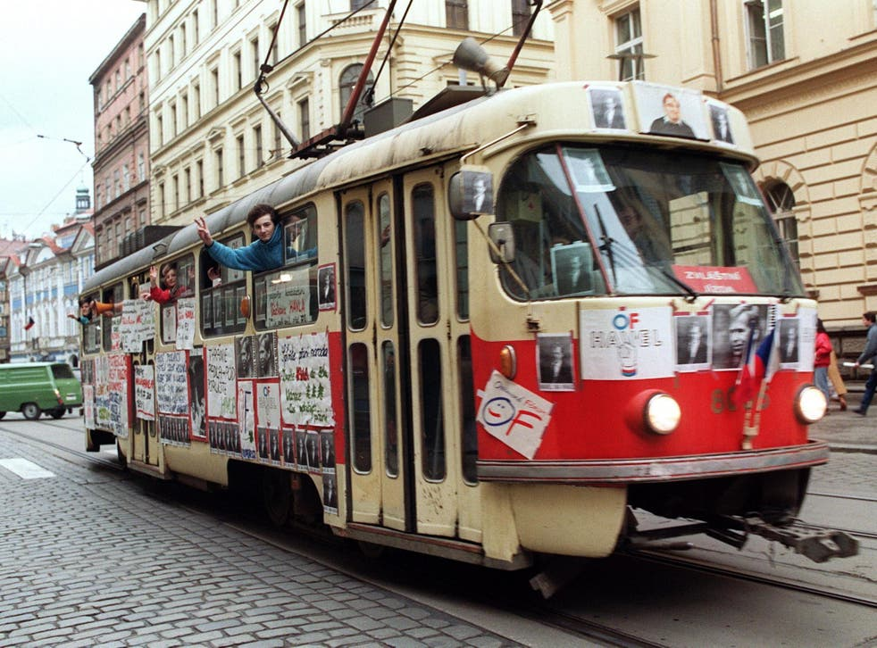 Young Czechoslovak people wave from a tramway in support of Vaclav Havel for presidency during a protest rally on 17 December 1989 near Wenceslas Square in Prague
