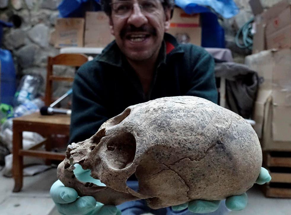 Archeologist Jedu Sagarnaga holds a skull as part of an archeological finding, dated approximately 500 years ago, in Mazo Cruz, near Viacha, Bolivia, November 12, 2018