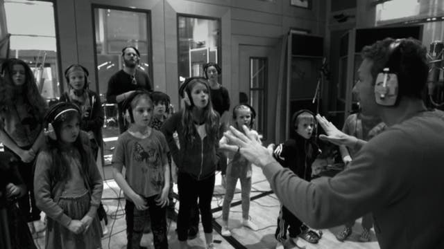 Chris Martin conducts a choir of children. The band's music has involved more choruses of voices in recent years