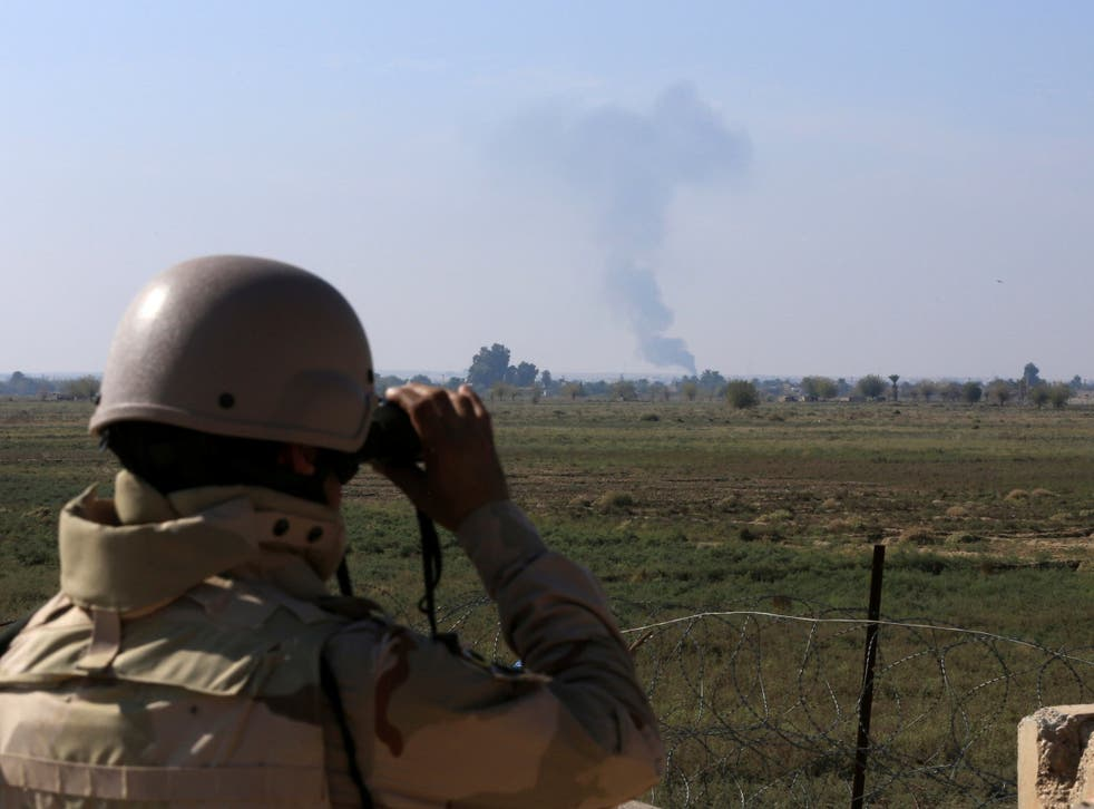 An Iraqi soldier watches smoke rising after an airstrike by US-led International coalition warplanes against ISIS, on the border between Syria and Iraq in Qaim, Anbar province, Iraq on 13 November 2018. (Hadi Mizban /