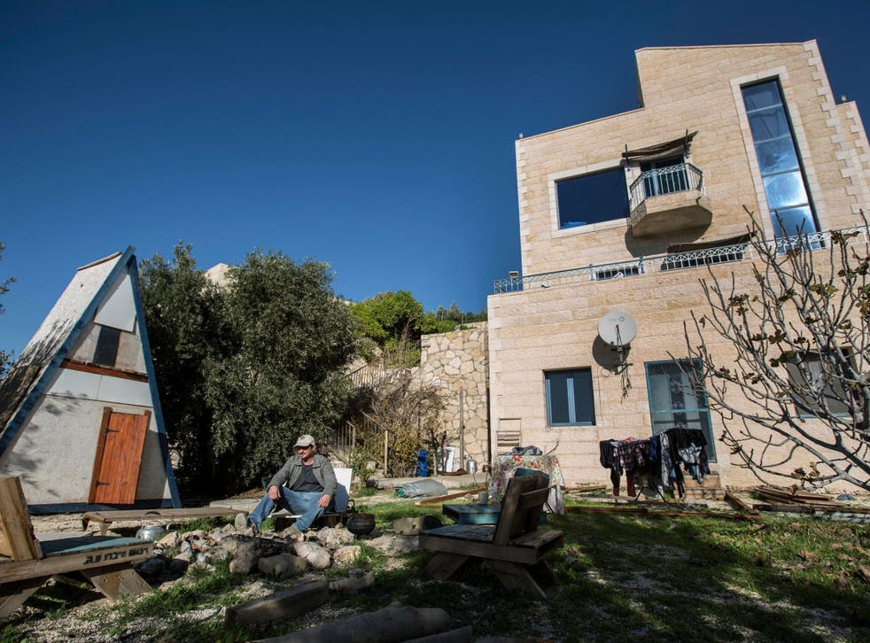 Moshe Gordon sits outside his guest house advertised on Airbnb, in the Nofei Prat settlement in the West Bank