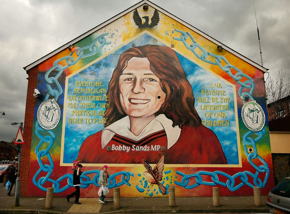 A couple walks past a mural of Bobby Sands in the Falls Road, Belfast. Republican Sands died in prison in 1981 after a 66-day hunger strike