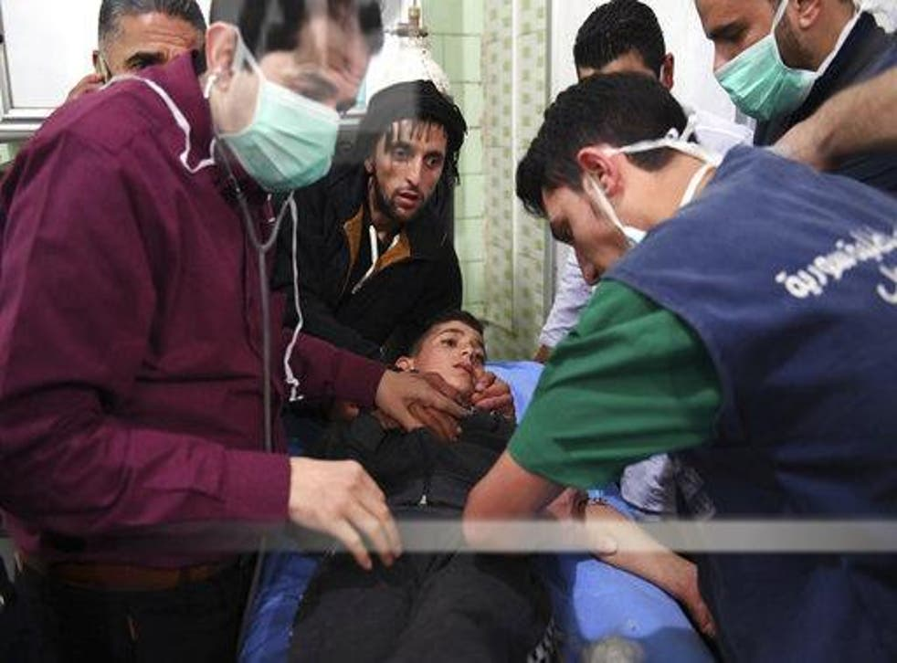 A boy is treated following the suspected chemical attack yesterday