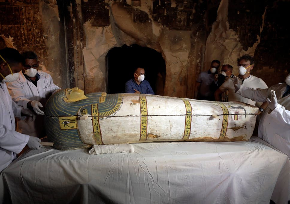 Archaeologists remove the cover of an intact sarcophagus inside a tomb in Luxor, Egypt