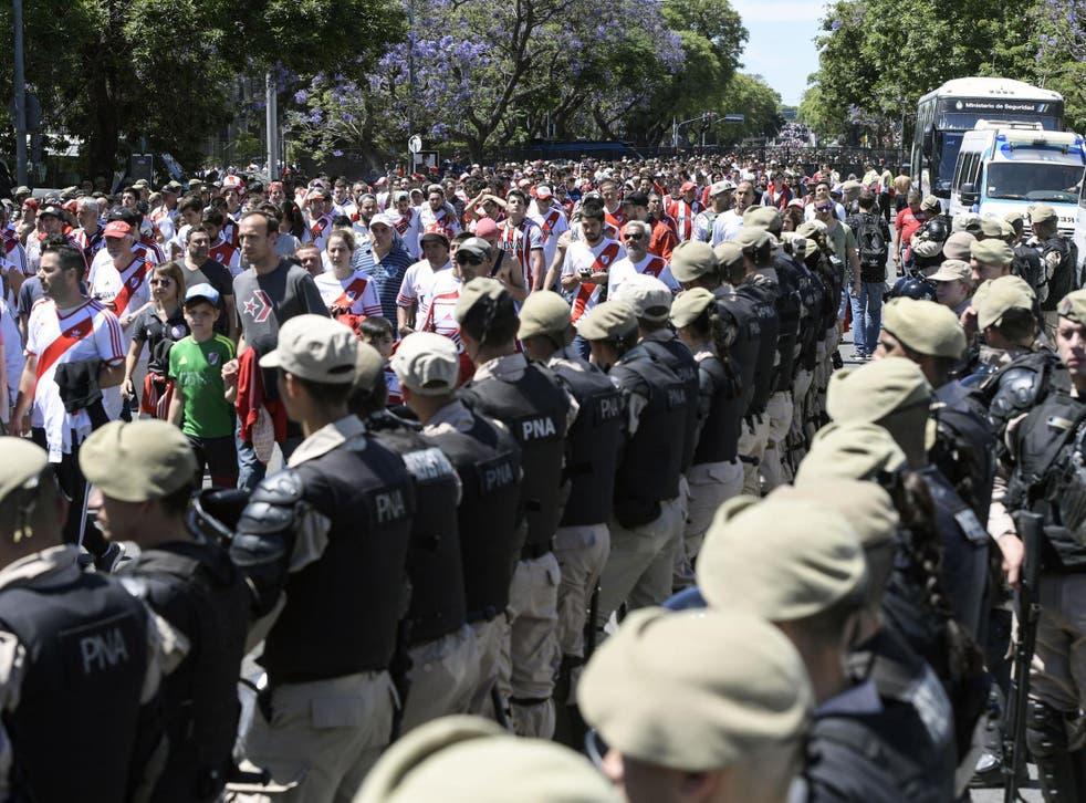 Security forces stand guard as River Plate's supporters leave Estadio Monumental
