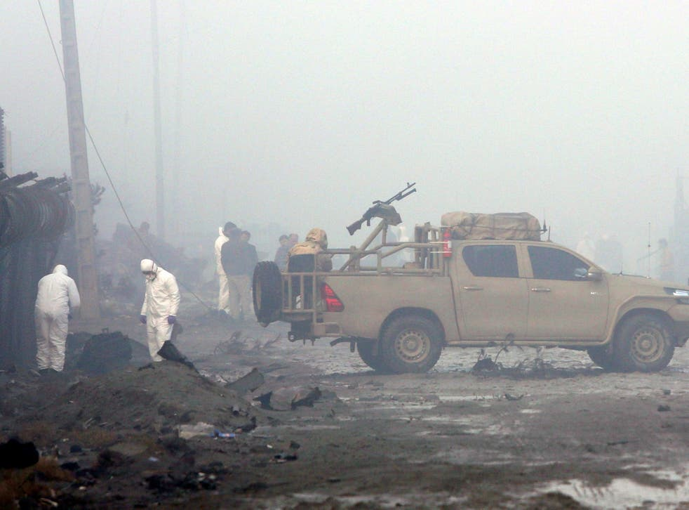 Afghan security forces inspect the site of a suicide bomb attack at a G4S compound in Kabul