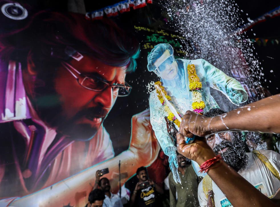 A person sprays milk as they celebrate the release Indian director and actor Rajinikanth's long awaited film '2.0' in Mumbai, India