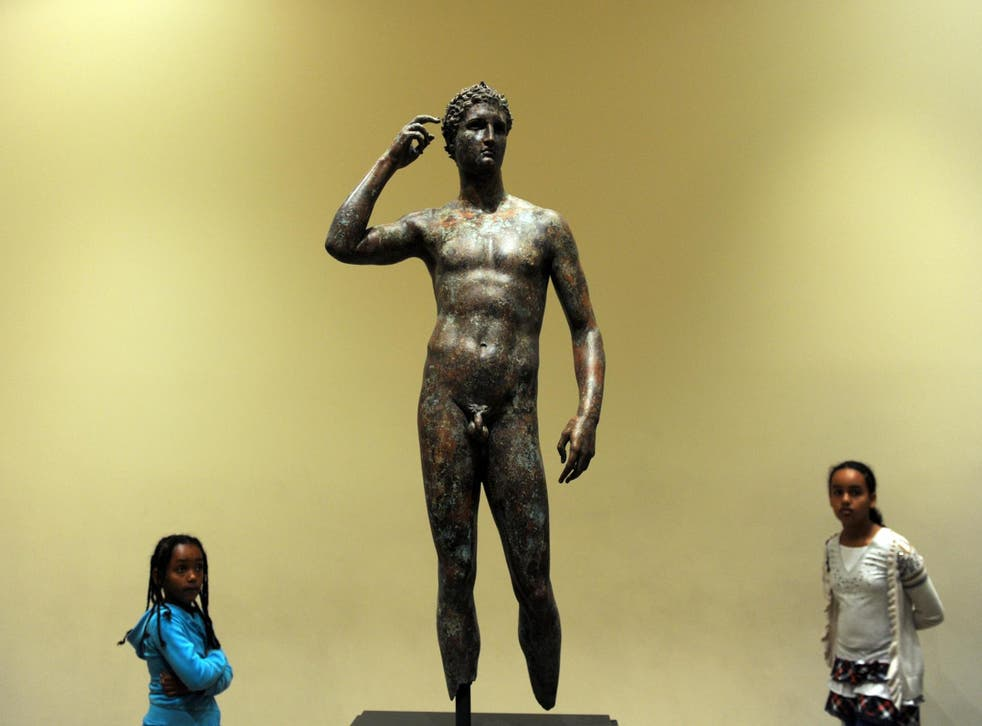 Visitors look on 18 April, 2011 at a statue of the Victorious Youth, which was recovered from a first-century BC shipwreck in the Adriatic Sea off the coast of Italy, at the Getty Villa Museum in Malibu, California.
