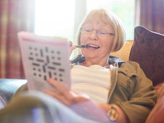 Woman doing crossword puzzle at home