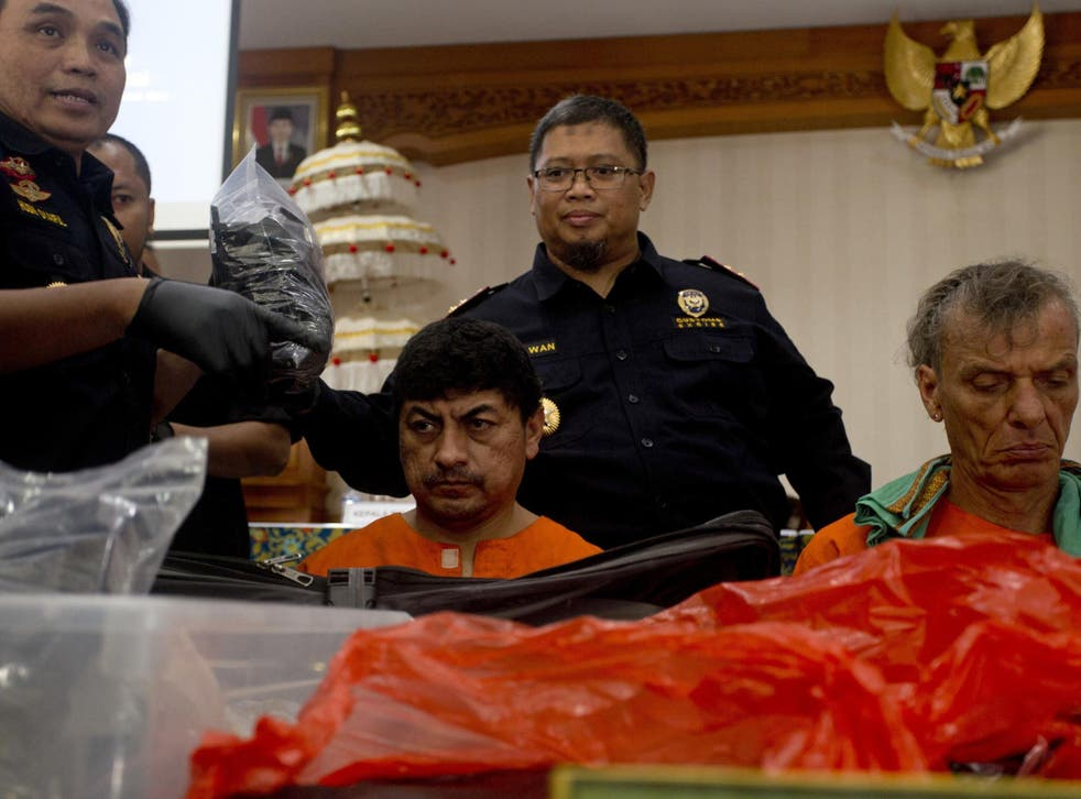 Indonesian customs officers display drug hauls in front of the Peruvian and the German suspects