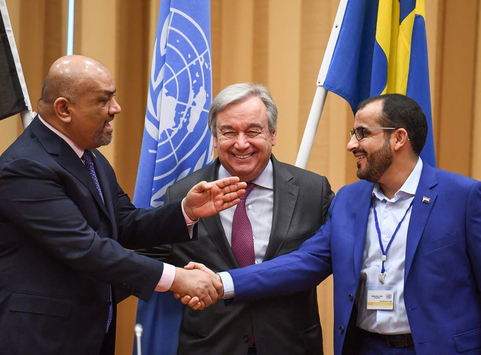 Yemen's foreign minister Khaled al-Yamani (left) and head rebel negotiator Mohammed Abdelsalam (right) shake hands under the eyes of UN Secretary General Antonio Guterres, during talks in Rimbo, north of Stockholm, on December 13