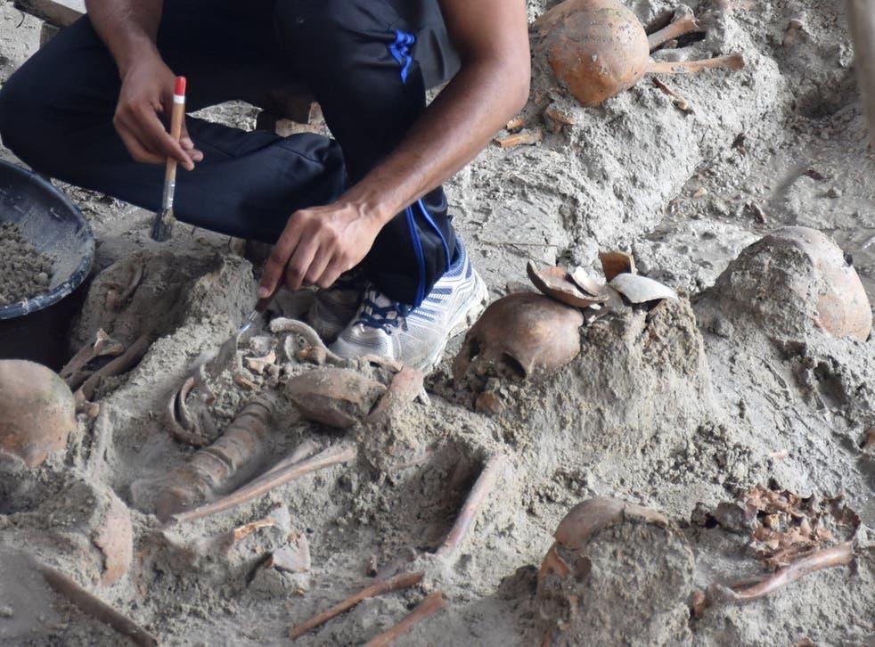 Staff dig up skeletons at a site of a former war zone in Mannar, Sri Lanka