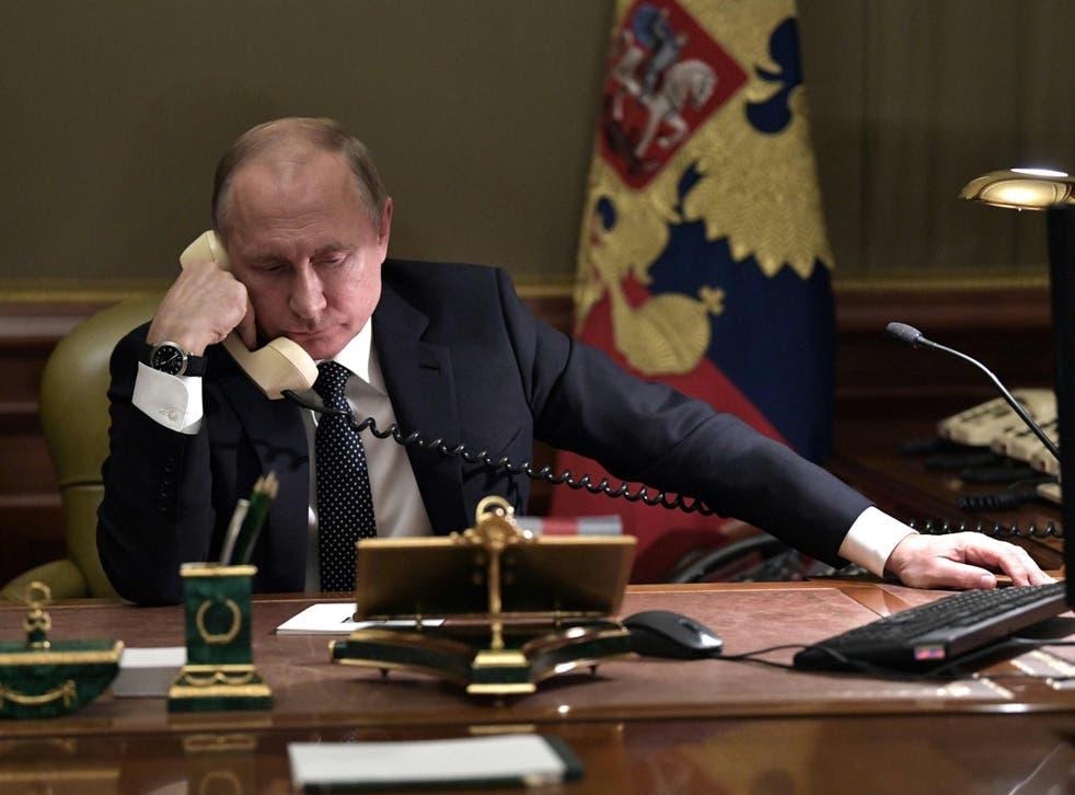 Vladimir Putin speaks on the phone in his office in Saint Petersburg