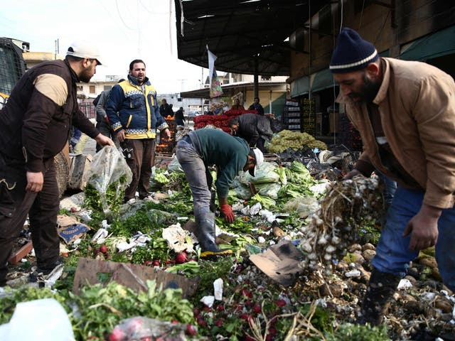 People try to salvage vegetables after a car bomb reportedly exploded near a position of pro-Turkey fighters in a market in the northern Syrian city of Afrin, on 16 December 2018 (Nazeer Al-Khatib /