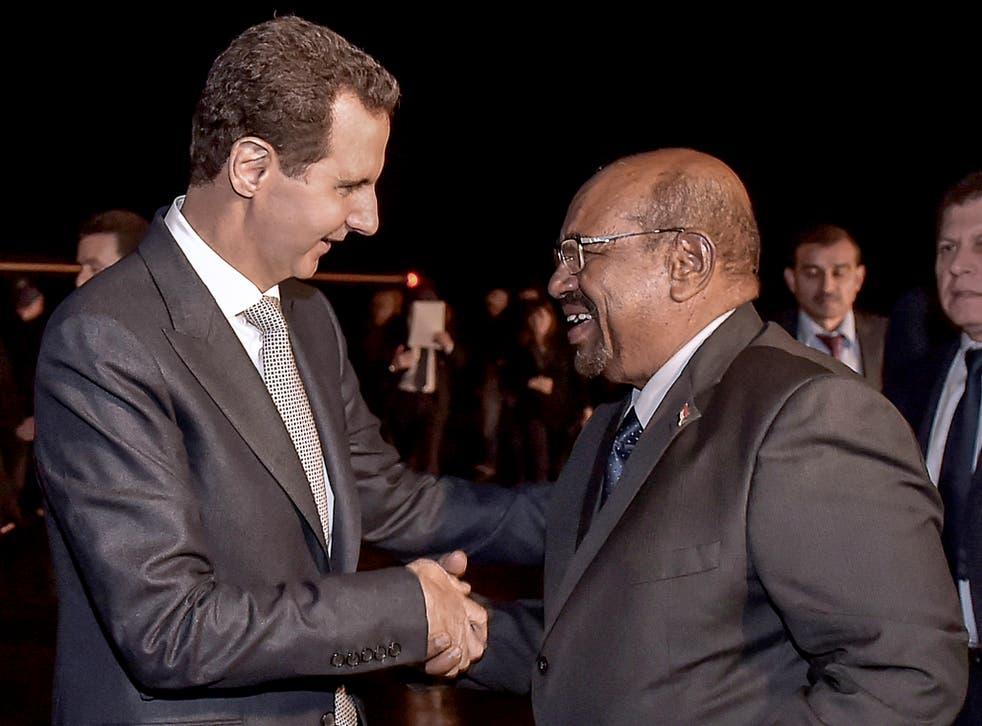 Criminal minds: Syrian president Bashar al-Assad, left, welcomes Omar al-Bashir at Damascus airport on Sunday