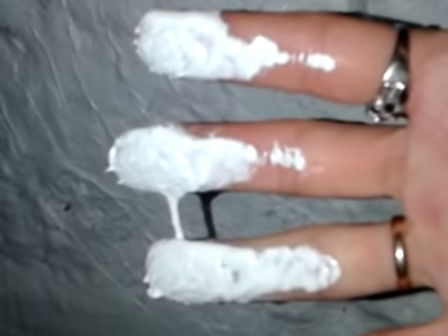 Woman shows what appears to be white paint on snow in Siberia