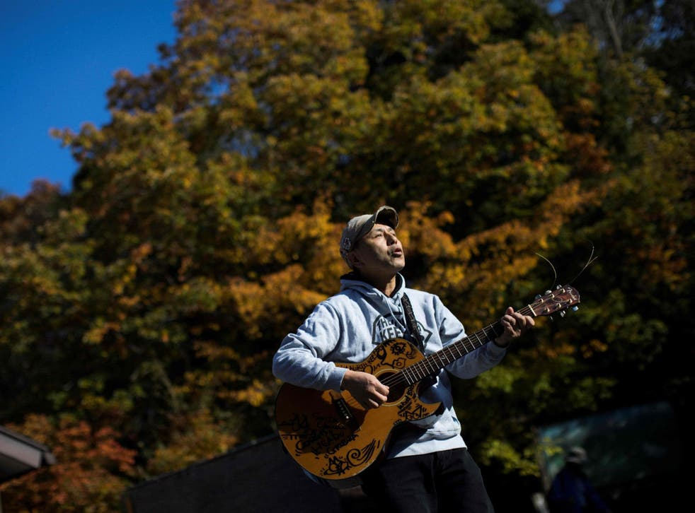 Kyochi Watanabe plays music into Aokigahara forest in the hope of lifting suicidal people out of despair