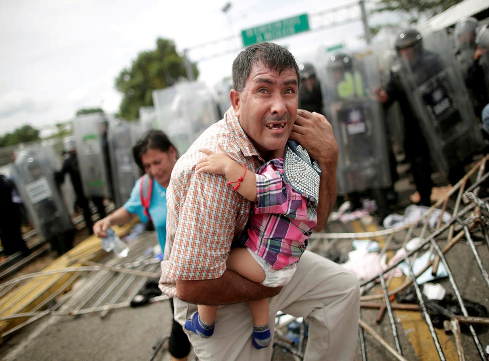 A Honduran migrant protects his child, as part of a caravan trying to reach the US stormed a border checkpoint in Guatemala near Mexico in October