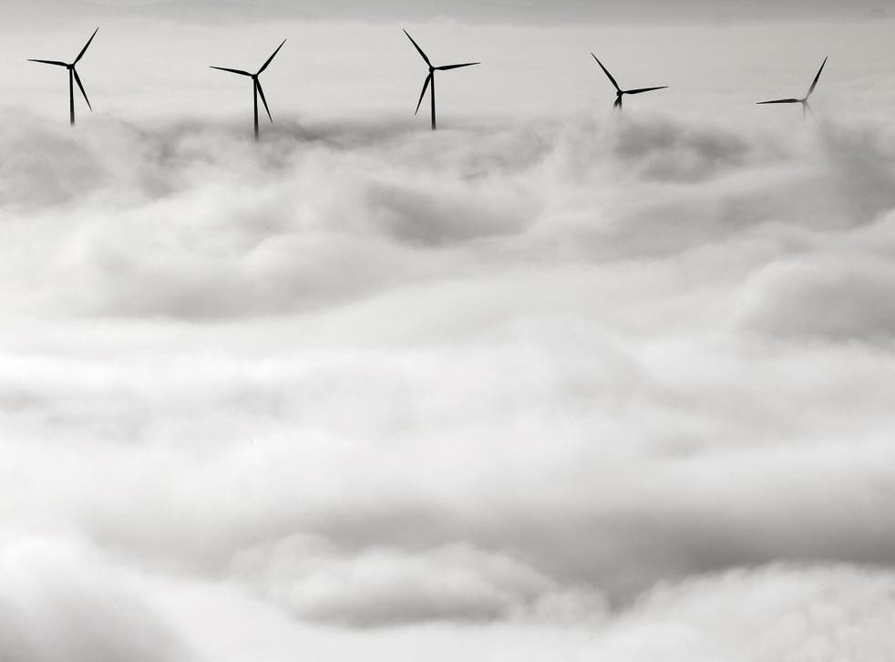 <p>Wind turbines stand out from a dense blanket of fog covering Pamplona, northern Spain</p>