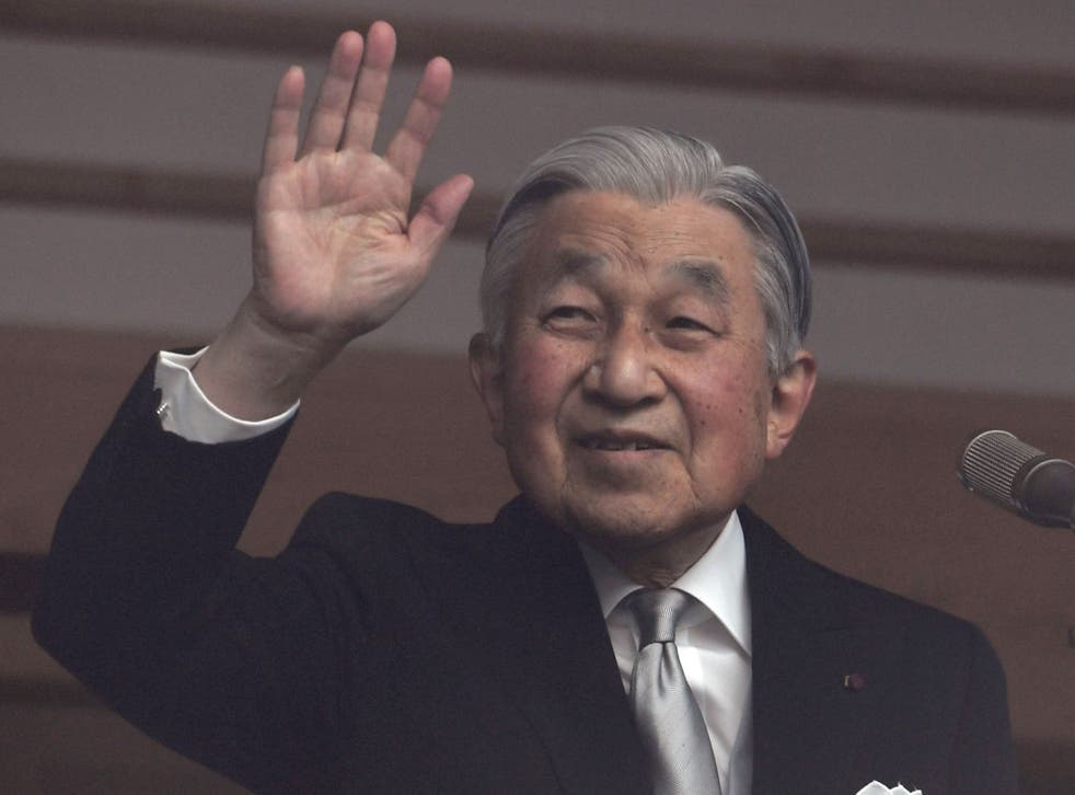 Emperor Akihito waves to well-wishers at the Imperial Palace on his 85th birthday