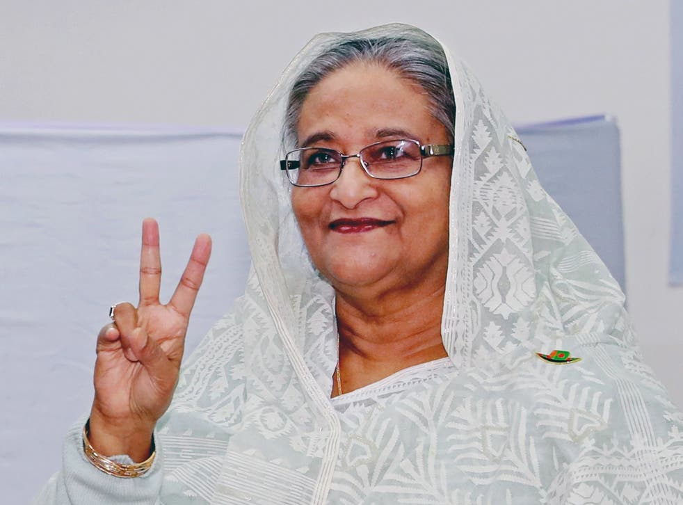 Bangladeshi prime minister Sheikh Hasina makes the victory signal after casting her vote at a polling station in Dhaka