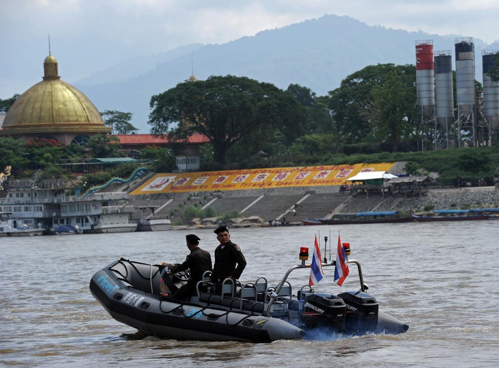 Thai police patrol the Mekong river, where the bodies of two men were found stuffed with concrete