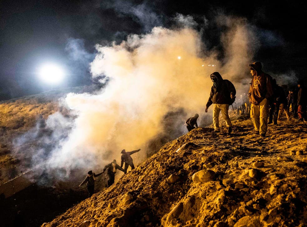 Central American migrants run away from tear gas thrown by the US border patrol