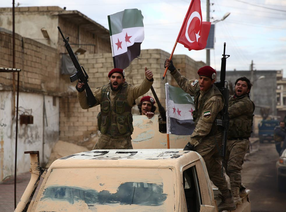 Turkish-backed Syrian fighters raise Turkish and opposition flags in the north of Aleppo province before heading to the Kurdish-controlled town of Manbij on 29 December