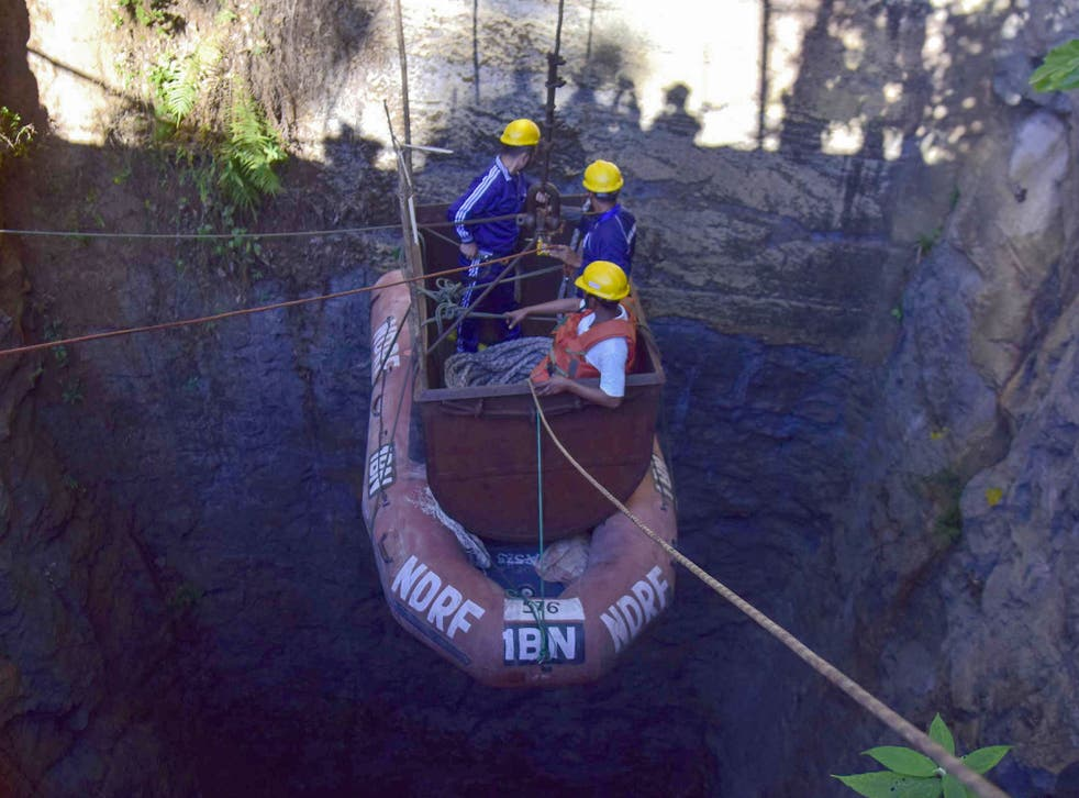 Indian Navy divers are lowered into the illegal coal pit in Meghalaya where 15 miners have been trapped for over three weeks as part of the rescue operation