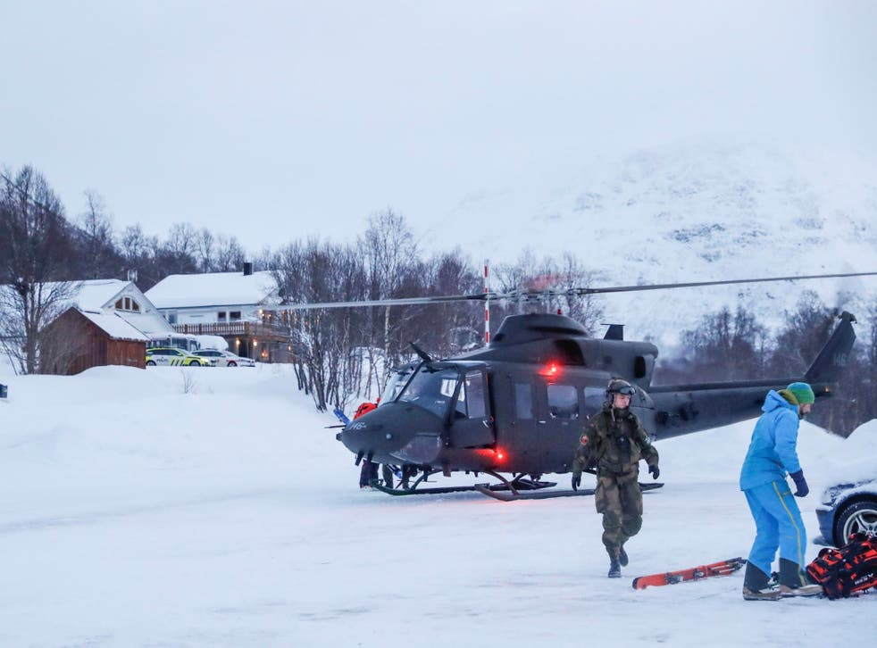 A military helicopter and rescue workers search for the skiers in Tamokdalen, northern Norway
