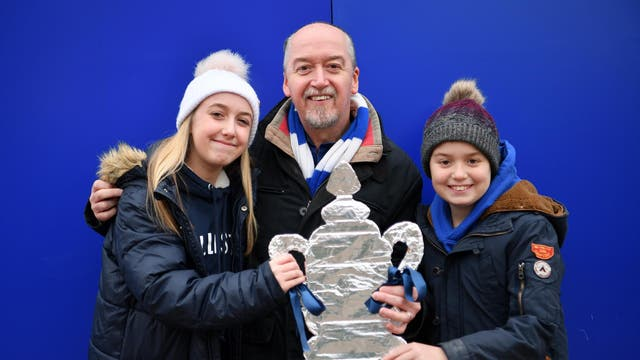 Fans pose with a homemade FA Cup trophy