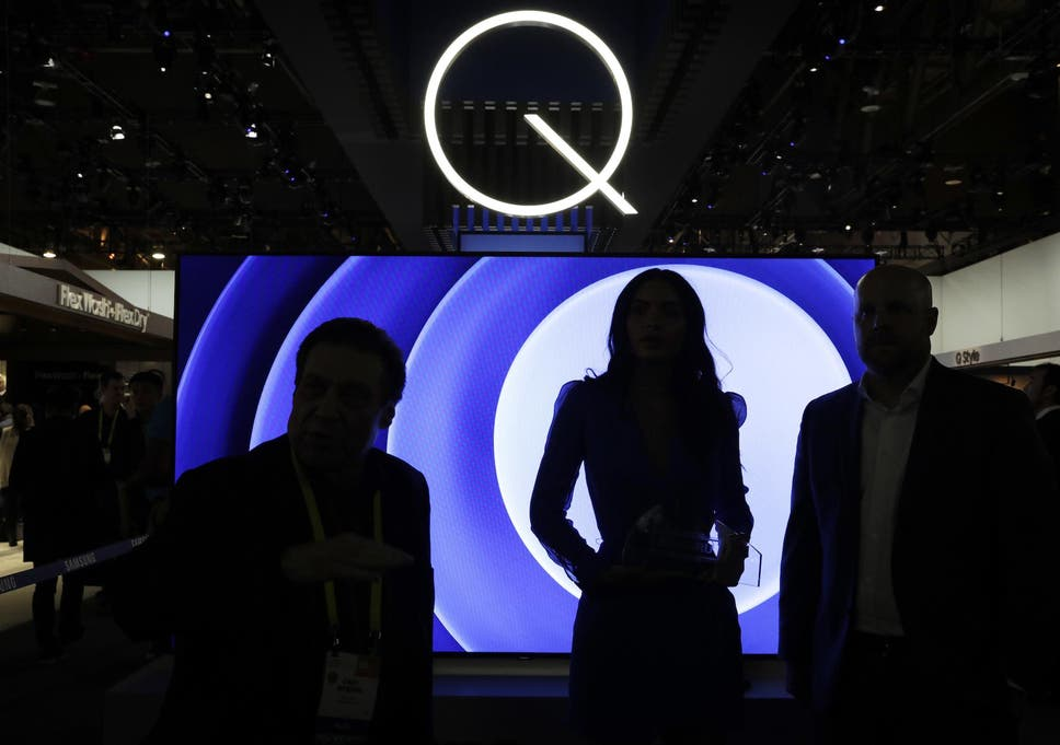 Attendees stand in front of a QLED TV at the Samsung booth during CES International in Las Vegas