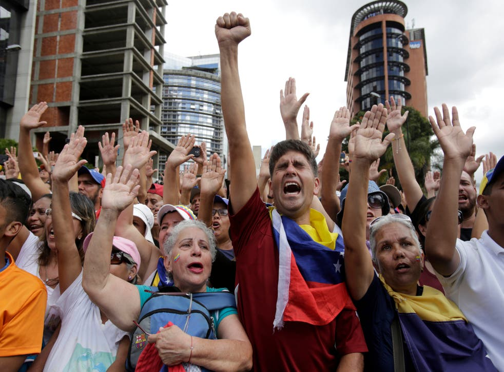 Anti-government protesters cheer after Juan Guaido, head of Venezuela's opposition-run congress, declared himself interim president