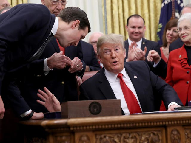 Pictured: Senior adviser to the President Jared Kushner (L) leans in to speak with US President Donald Trump during the signing ceremony for the First Step Act and the Juvenile Justice Reform Act in the Oval Office of the White House 21 December 2018 in Washington, DC.