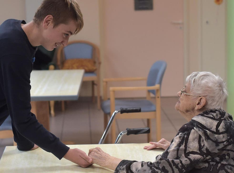 A teennager with psychological difficulties (L) holds the hand of a woman with Alzheimer's disease in a retirement home on 18 October 2016 in Saint Quirin, eastern France.