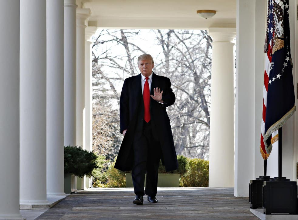 President Donald Trump waves as he walks through the Colonnade from the Oval Office of the White House
