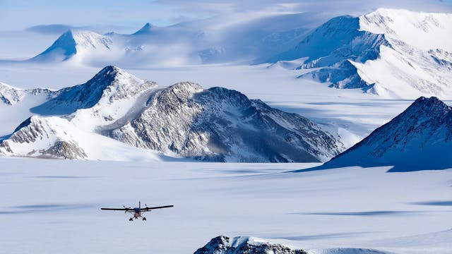 A Twin Otter airplane during a reconnaissance flight over the Antarctic Plateau and the Edson Glacier in the Ellsworth Mountains. This utility airplane, equipped with wheels or skis, adapts perfectly to the Antarctic environment with its rugged construction and short take off and landing performance