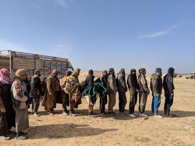 Men who fled the last Isis-held area of Syria line up to be questioned by American and Kurdish intelligence officials