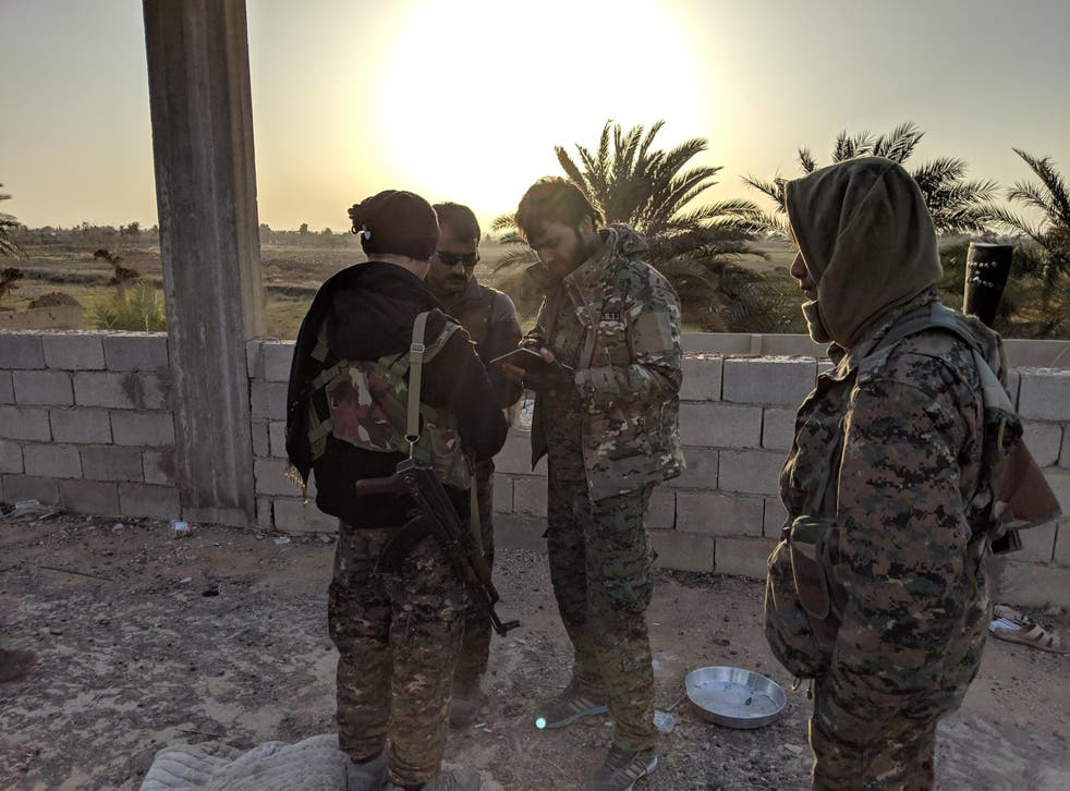 SDF fighters gather near the frontline against Isis in the village of Baghouz Tahtani, eaastern Syria.