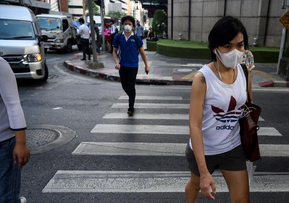 People, wearing face masks, make their way along a street in Bangkok