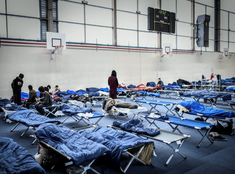 Migrants stay at the Jean-Bouin gymnasium, western Paris, which has been requisitionned to welcome 150 migrants, on January 31, 2019 /