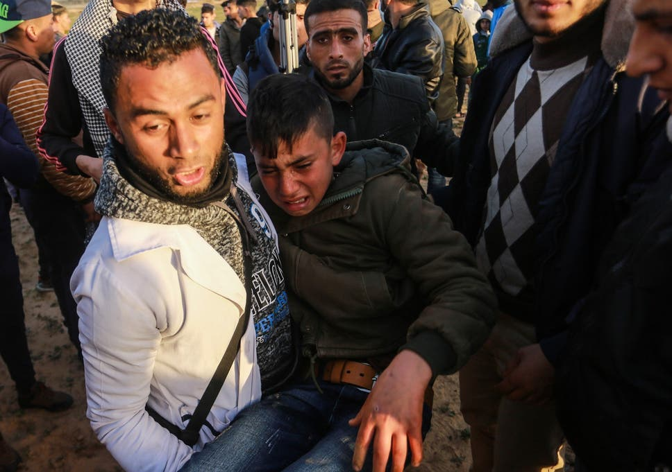 An injured Palestinian carried away during border protest