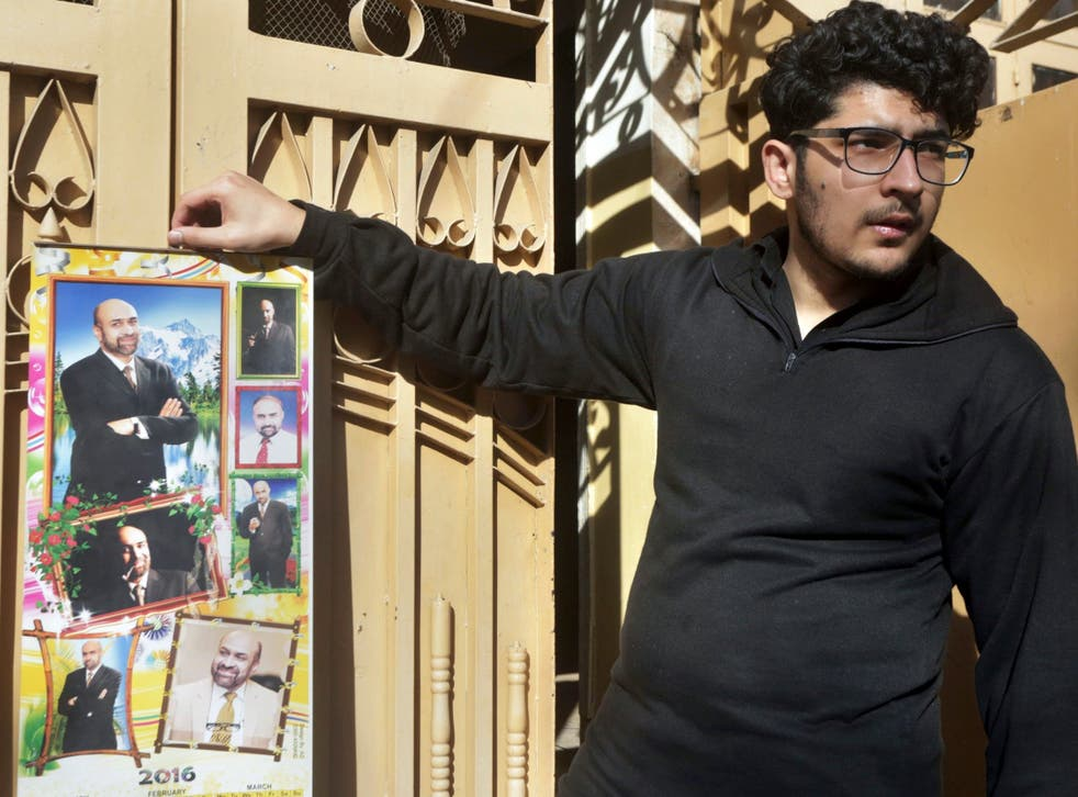 Pictured: Osama Rizi, son of journalist Rizwan-ur-Rehman Razi, displays a calendar with pictures of his father outside his residence in Lahore, Pakistan, Saturday 9 February 2019.