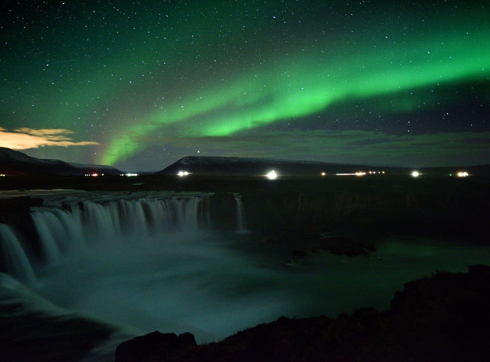 The Northern Lights over Godafoss waterfall in Iceland